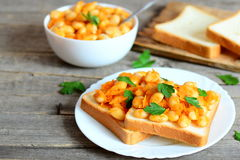 Baked white beans with vegetables on bread and on plate Royalty Free Stock Photo
