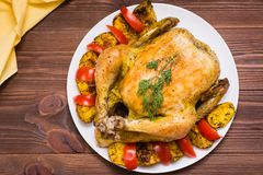Baked whole chicken with a garnish of potatoes and tomatoes. On a plate. Top view royalty free stock photos