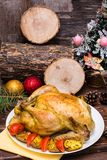 Baked whole chicken with a garnish of potatoes and tomatoes. On a plate. Christmas decoration royalty free stock photography