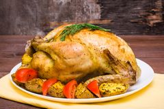 Baked whole chicken with a garnish of potatoes and tomatoes. On a plate stock photography