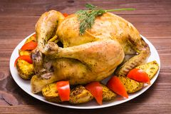 Baked whole chicken with a garnish of potatoes and tomatoes. On a plate stock images