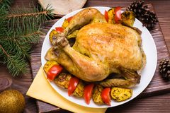 Baked whole chicken with a garnish of potatoes and tomatoes. On a plate. Christmas decoration royalty free stock photos