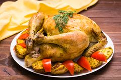 Baked whole chicken with a garnish of potatoes and tomatoes. On a plate. Wooden table stock image