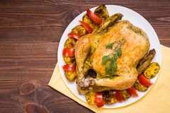 Baked whole chicken with a garnish of potatoes and tomatoes. On a plate. Wooden table. Top view stock photo