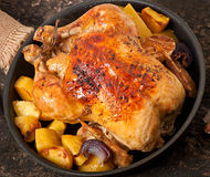 Baked whole chicken with potatoes Stock Photo