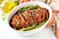 Baked whole pork meat with tomatoes, green beans and black olives, homemade cozy winter dish in a pot. Christmas tasty food. Baked whole pork meat with tomatoes stock image