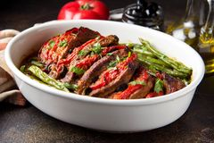 Baked whole pork meat with tomatoes, green beans and black olives, homemade cozy winter dish in a pot. Christmas tasty food. Baked whole pork meat with tomatoes royalty free stock image