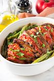 Baked whole pork meat with tomatoes, green beans and black olives, homemade cozy winter dish in a pot. Christmas tasty food. Baked whole pork meat with tomatoes stock images