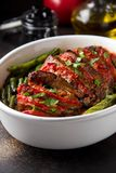 Baked whole pork meat with tomatoes, green beans and black olives, homemade cozy winter dish in a pot. Christmas tasty food. Baked whole pork meat with tomatoes stock photos