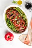 Baked whole pork meat with tomatoes, green beans and black olives, homemade cozy winter dish in a pot. Christmas tasty food. Baked whole pork meat with tomatoes royalty free stock photography