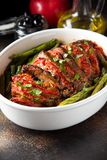Baked whole pork meat with tomatoes, green beans and black olives, homemade cozy winter dish in a pot. Christmas tasty food. Baked whole pork meat with tomatoes royalty free stock photo