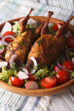 Baked whole quail and fresh vegetables close-up. vertical. Baked whole quail and fresh vegetables close-up on a plate. vertical Royalty Free Stock Photos