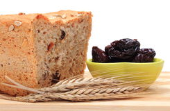 Baked wholemeal bread, dried plums and ears of wheat Stock Photography