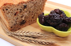 Baked wholemeal bread, dried plums and ears of wheat Royalty Free Stock Photos
