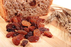Baked wholemeal bread, raisins and ears of wheat Stock Images