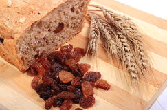 Baked wholemeal bread, raisins and ears of wheat Stock Image