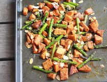 Baked Yams with Asparagus. A light and delicious summertime dish. Diced yams and asparagus tossed in olive oil with oregano, garlic, paprika, salt and pepper royalty free stock images