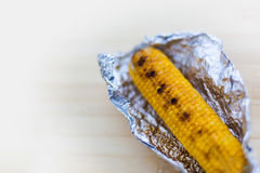 Baked yellow corn in foil on white background Stock Photography