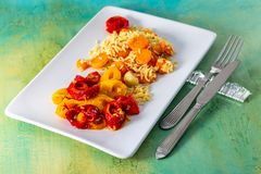 Baked yellow red pepper and cooked white rice with delicious carrots on a white ceramic plate royalty free stock photo
