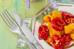Baked yellow red peppers on a silver plate and fork and knife. stock photo