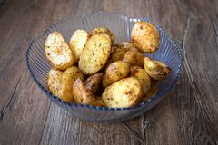 Baked young organic potatoes in a glass bowl. On vintage wooden table royalty free stock photography