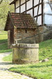 Bakehouse Granary, Freilichtmuseum Hessenpark. An old draw well nearby Bakehouse Granary located in the open-air museum Hessenpark, Germany Stock Photos