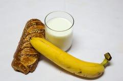 Bakelse, bananen och exponeringsglas av mjölkar isolerat på vit bakgrund Royaltyfri Bild