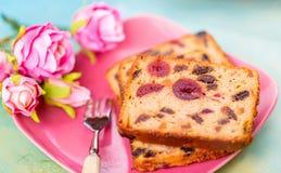 bakelser En kakaskiva med frukter p? en rosa platta Fruktkakarussin och k?rsb?r royaltyfri foto