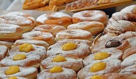 Bakelser med vaniljkräm och socker på försäljning från bagerier Arkivfoto