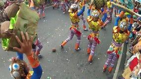 Baken av unga män och kvinnor i utsmyckad kokosnötdräkt ståtar längs gatan, en festival för att hedra en skyddshelgon