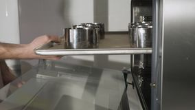 Baker βάζει στους ρόλους κανέλας σε ένα τηγάνι ψησίματος στο φούρνο που ψήνει απόθεμα βίντεο