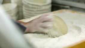 Baker κυλά τη ζύμη στο αλεύρι απόθεμα βίντεο