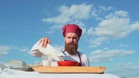 Baker με ποικίλες υγιείς και εύγευστες πρόσφατα ψημένες ψωμί και ζύμη Χαμογελώντας αρσενικό χύνοντας αλεύρι αρτοποιών εύθυμος φιλμ μικρού μήκους