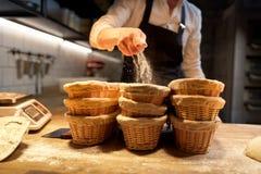 Baker με τα καλάθια για τη ζύμη που αυξάνεται στο αρτοποιείο Στοκ Εικόνα