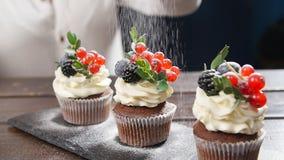 Baker που διακοσμεί το νόστιμο cupcake Ζάχαρη τήξης που ψεκάζεται στο κέικ φιλμ μικρού μήκους