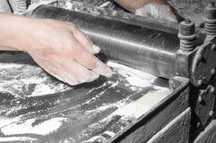 Baker που κατασκευάζει τη ζύμη στο sheeter στοκ εικόνα