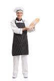 Baker που κρατά μια φραντζόλα του ψωμιού στοκ εικόνα