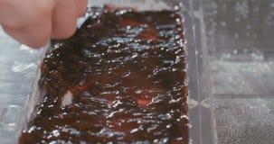 Baker που προετοιμάζει cheesecake με τη μαρμελάδα βακκινίων απόθεμα βίντεο
