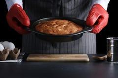 Baker που φορά την κόκκινη πίτα λαβής potholder έννοια συνταγής στοκ φωτογραφία