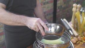 Baker που χύνει το άσπρο αλεύρι στο κόσκινο για το κοσκίνισμα στον ξύλινο πίνακα Μάγειρας αρχιμαγείρων που ψεκάζει τη σκόνη αλευρ απόθεμα βίντεο