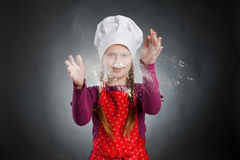 Baker. An image of a funny little girl in white hat stock photography