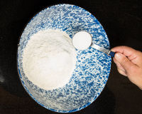 Baker adding salt to bread mix. A baker adding salt to bread mix in a bowl Royalty Free Stock Images