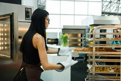 Baker adds freshly baked bakery products from the oven on the shelves stock image