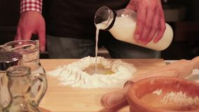 Baker adds milk to the dough. Traditional cook adds milk to the bread dough stock footage