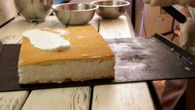 Baker appliquant la crème blanche sur le gâteau banque de vidéos