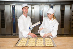 Baker apprentice and instructor in bakery Stock Photos