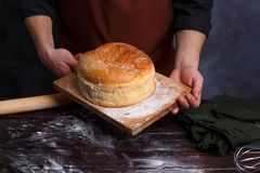 Baker in apron holding board with hot freshly baked bread at kit stock photos