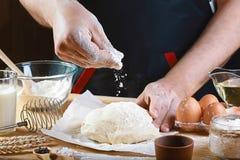 Baker arrosent la pâte avec des ingrédients de recette de pain, de pizza ou de tarte de farine avec les mains, nourriture sur le  photographie stock