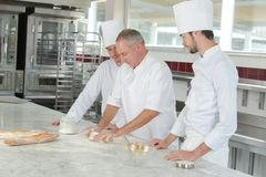 Baker and assistants in bakery kitchen. Baker and assistants in a bakery kitchen stock photo