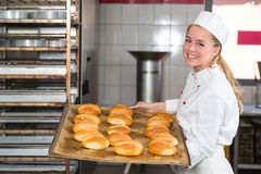 Baker in bakehouse or bakery posing with tray of fresh bread. Baker in bakehouse or bakery posing with tray of buns and bread Stock Photos